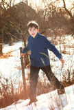 Handsome preteen boy on the country sunny spring snowy backgroun Stock Image