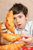 Handsome preteen boy play with croissan imagine its a  sheep Royalty Free Stock Image