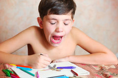 Handsome preteen boy yawn while drawing Royalty Free Stock Photos