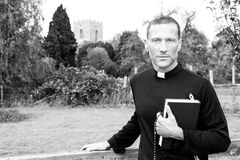 Handsome priest standing next to country gate while holding his bible with church and field in background royalty free stock image