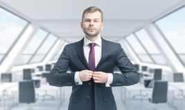A handsome professional is buttoning up the suit. Bright modern panoramic roof loft office. Stock Photo