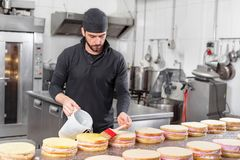Handsome professional confectioner making a batch of delicious cake in the pastry shop. Handsome professional confectioner making a batch of delicious cake in royalty free stock photo