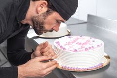 Handsome professional confectioner making a delicious cake in the pastry shop. Handsome professional confectioner making a delicious cake in the pastry shop stock photos