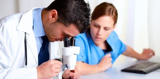 Handsome professional medical using a microscope. Portrait of a handsome professional medical using a microscope with a pretty nurse at hospital Royalty Free Stock Photos
