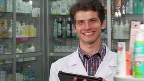 Handsome professional pharmacist doing inventory using digital tablet stock photo