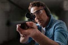 Handsome professional sniper looking into the optical sight. Professional shooter. Handsome professional male sniper holding a gun and looking into the optical Royalty Free Stock Photography