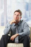 Handsome professional thinking on sofa Royalty Free Stock Photography