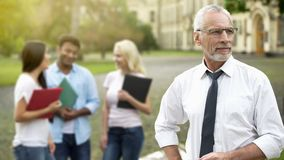 Handsome professor looking into distance students on background higher education. Stock photo stock photography