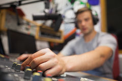 Handsome radio host moderating touching switch. In studio at college Stock Image