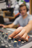 Handsome radio host moderating turning up volume. In studio at college Stock Image
