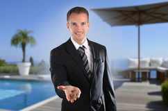 Handsome real estate agent in front of luxury villa with real-estate agent. Handsome real estate agent holding a key in front of luxury villa with real-estate stock images