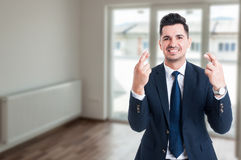 Handsome real estate agent wishing good luck. And holding fingers crossed with copy space Royalty Free Stock Photo