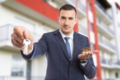 Handsome realtor holding house and apartment keys. Handsome realtor holding house and giving apartment keys as new home offer concept on flat building backgound Royalty Free Stock Image