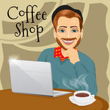 Handsome red haired hipster man with laptop enjoying a hot coffee in coffee shop Stock Photography