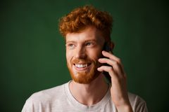 Handsome redhead bearded man talking on phone Stock Photography