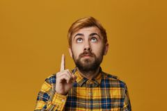 Handsome redhead dyed bearded male point with finger above and looking there seriously. Isolated over yellow background royalty free stock photography
