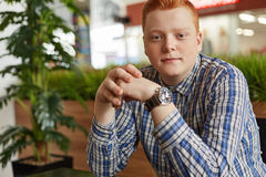 A handsome redhead freckled boy in checked shirt sitting in cosy restaurant with green plantation holding his hands together havin Royalty Free Stock Image
