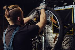 Handsome redhead male in a jeans coverall, working with a bicycle wheel in a repair shop. A worker removes the bicycle. A handsome redhead male in a jeans Royalty Free Stock Image