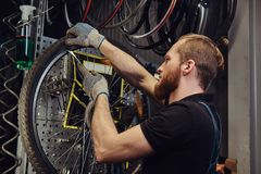 Handsome redhead male in a jeans coverall, working with a bicycle wheel in a repair shop. A worker removes the bicycle. A handsome redhead male in a jeans Stock Image