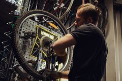 Handsome redhead male in a jeans coverall, working with a bicycle wheel in a repair shop. A worker removes the bicycle. A handsome redhead male in a jeans Stock Photos