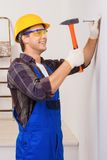 Handsome repairman nailing. Young smiling repairman in eyewear and helmet nailing with the help of hammer Stock Photography