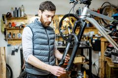 Man repairing a bicycle in the workshop stock photos