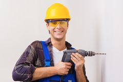 Handsome repairman using drill Royalty Free Stock Images