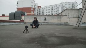 Handsome reporter shooting a video by himself on the street roof. 4K