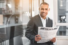 Handsome respectable guy reading print media. Waist up portrait of Young African businessman standing near window of office. Guy looking at camera with smile stock images