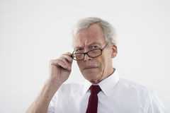 Handsome retired man in glasses. Peering over the top of the frames at the camera with a frown, head and shoulders studio portrait Stock Images
