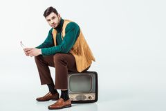 Handsome retro styled man sitting on vintage television and looking at camera. On white Stock Photos