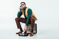 Handsome retro styled man sitting on vintage television and talking by stationary. Telephone Royalty Free Stock Photo
