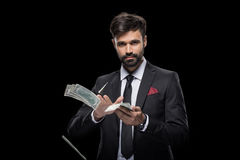 Handsome rich businessman throwing dollar banknotes royalty free stock photo
