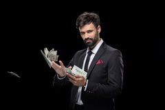 Handsome rich businessman throwing dollar banknotes stock photo