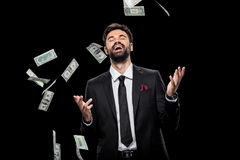 Handsome rich excited businessman throwing dollar banknotes, Stock Photo