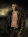 Handsome Robotic Man Wearing Leather Jacket. Young Handsome Robotic Man Wearing Leather Jacket Showing Sexy Body Abs While Looking at the Camera on Crashed City Royalty Free Stock Image