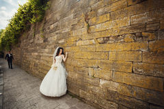 Handsome romantic groom and beautiful brunette bride near ol Stock Images