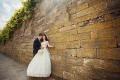 Handsome romantic groom kissing beautiful brunette bride near ol Royalty Free Stock Image