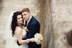 Handsome romantic groom kissing beautiful brunette bride near ol Stock Image