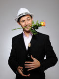 Handsome romantic man with rose flower and vine. Handsome romantic young man holding rose flower and vine bottle  prepared for a date. gray background Royalty Free Stock Photo