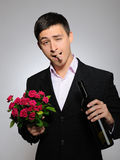 Handsome romantic man with rose flower,vine bottle Royalty Free Stock Photos