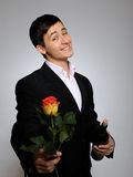 Handsome romantic young man with rose flower Stock Image