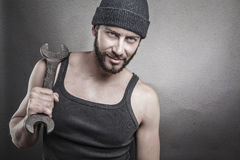 Handsome rough man holding a wrench over a textured grey backgro Royalty Free Stock Photography