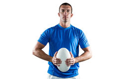 Handsome rugby player in blue jersey holding ball Royalty Free Stock Images
