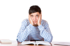 Handsome sad male student learns with study books Royalty Free Stock Images