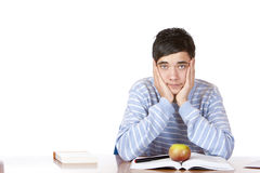 Handsome sad male student learns with study books. Young student sitting on desk and learns for his exams. He looks sad and tired into camera. Isolated on white Stock Images
