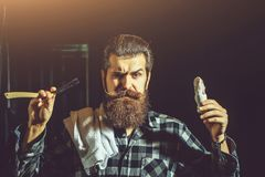 Bearded man shaves with razor. Handsome sad man, bearded hipster, brunette with long beard and moustache shaves with open vintage razor with blade and shaving royalty free stock photography