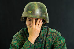 Handsome sad young soldier wearing uniform suffering from stress with his hand covering his face, in a black background.  Stock Photo