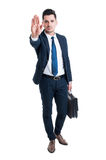 Handsome sales man showing stop gesture. Standing and holding a briefcase isolated on white background Stock Photography