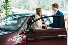 Handsome sales Manager shaking hands to customer after selling a car stock photos